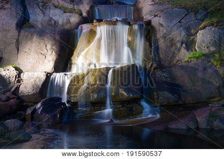 Cascades waterfall in Sapokka water garden the June night. Kotka, Finland