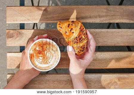 Woman holding a paper cup with coffee and chocolate croissant. Coffee to go. Tasty hot beverage on wooden table in sunny day. Outdoors meal. Flat lay top view.