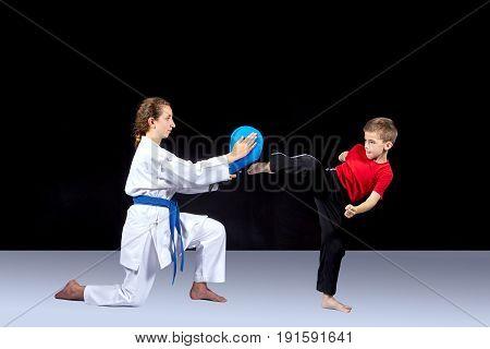 Girl athlete helps a sportsman train a kick
