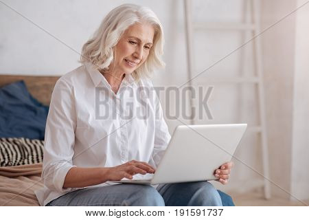 Being online. Delighted pleasant smart elderly woman holding a laptop and surfing the Internet while sitting on the bed