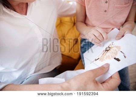 Hand made beauty. Close up of an embroided flower being in hands of nice positive grandmother and granddaughter