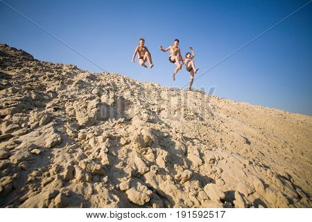 Kiev - August 21: Three boys jump from a slide of sand near the Dnieper River on August 21 2008 in Kiev Ukraine
