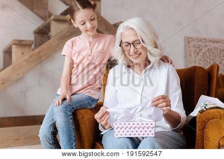 Pleasant surprise. Happy delighted joyful woman holding a gift box and opening it while sitting with her granddaughter