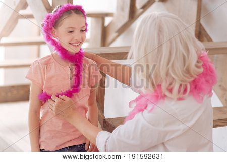 How do I look. Positive happy cute girl wearing a pink feather scarf and laughing while having a great time with her grandmother