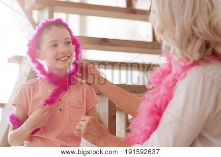 My family. Joyful positive pretty girl wearing a pink feather boa and looking at the grandmother while having a great time with her