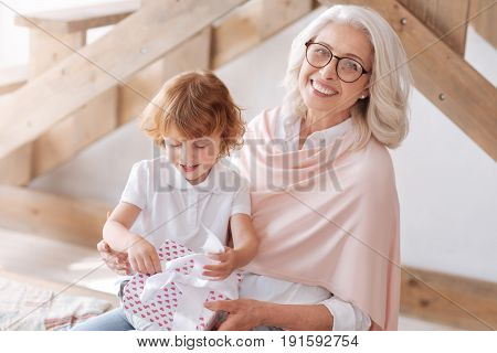 It is for me. Cute happy impatient boy sitting on his grandmothers laps and looking at his present while opening it