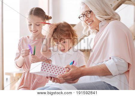Loving grandmother. Happy delighted joyful woman holding a gift box and smiling while giving presents to her grandchildren