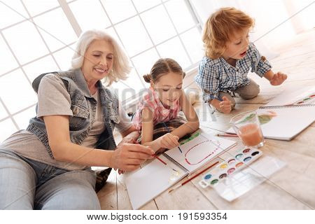 Family activity. Nice happy delighted family lying together on the floor and painting while feeling comfortable