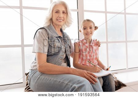 Love and care. Nice pleasant elderly woman smiling and hugging her granddaughter while sitting with her