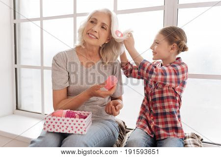 For curly hair. Positive delighted elderly woman holding a box with hair rollers and giving one of them to her granddaughter while having her hair style done