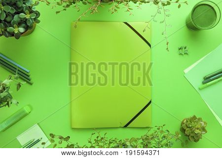 Overhead view of folder and office supplies on desk with file, supplies, green algae drink and plants. Living green and save the environment. Top view with copy space.