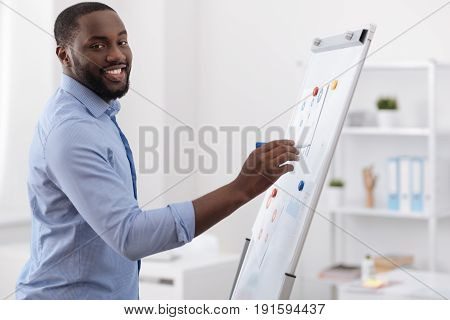 Visual explanation. Nice positive delighted man standing in front of the whiteboard and drawing a scheme while presenting his project
