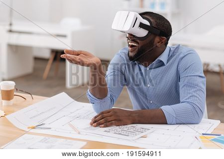 Innovative technology. Delighted handsome nice man wearing 3d glasses and testing them while using innovative technology