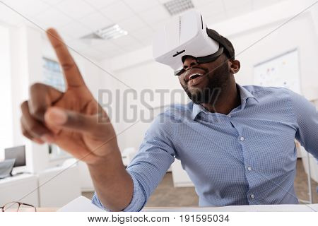 Future technology. Handsome nice Afro American man sitting at the table and touching the virtual screen while experiencing virtual reality