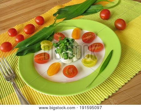 Ramsons cream cheese with tomatoes on plate