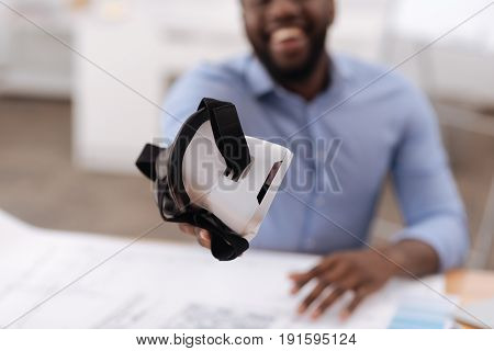 Take it. Selective focus of modern 3d glasses being in hands of a nice Afro american man while being given to you