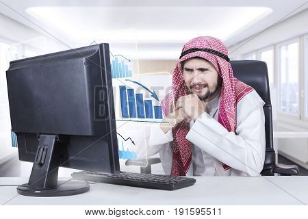Picture of a middle eastern businessman looks frustrated with a virtual declining graph on computer in the workplace