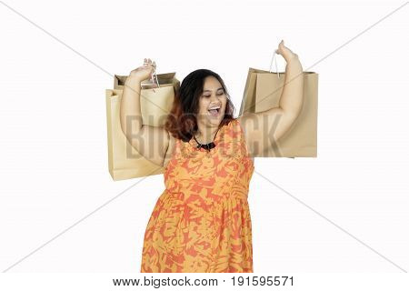 Cheerful woman lifting hands while holding shopping bags isolated on white background