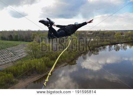Rope jumping from high altitude of bridge. Man fly in air like an airplane