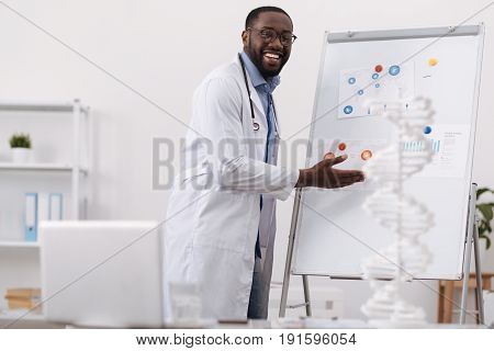 My research. Cheerful positive delighted man smiling and pointing at the whiteboard while presenting his research