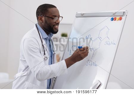 Chemical formula. Smart cheerful good looking scientist holding a highlighter and writing a chemical formula on the whiteboard while doing a research