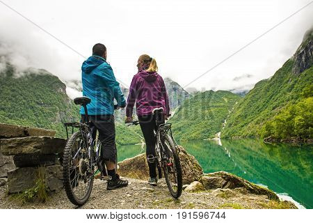 Biking couple in Norway against picturesque landscape