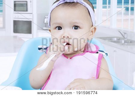 Cute female infant sitting on a high chair and bites a porridge spoon with dirty face in the kitchen