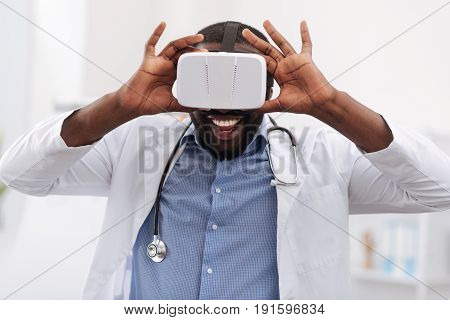 Developments in medicine. Cheerful delighted experienced doctor smiling and holding virtual reality glasses while using them