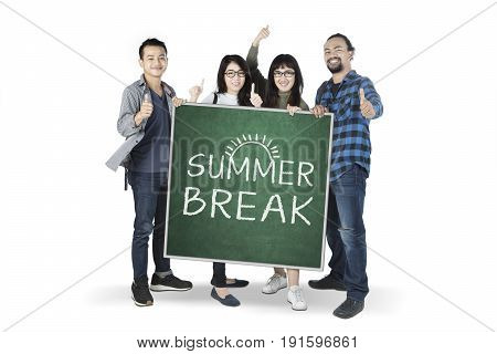 Diversity students showing thumbs up and holding a chalkboard with text of summer break in the studio