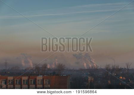 View of the city against the background of smoke and smog. Environmental pollution. Harm to health.