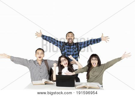 Diversity students showing happy expression by lifting hands while studying with a laptop and book on the table