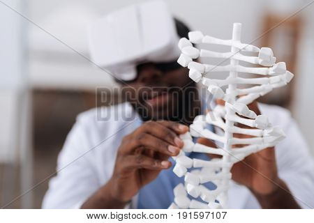 Genomics studies. Selective focus of a gene model standing on the table while being studied by a skillful professional male biologist