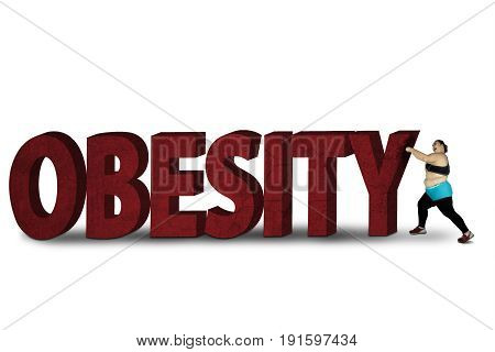 Fat woman crushing word of obesity while wearing sportswear isolated on white background