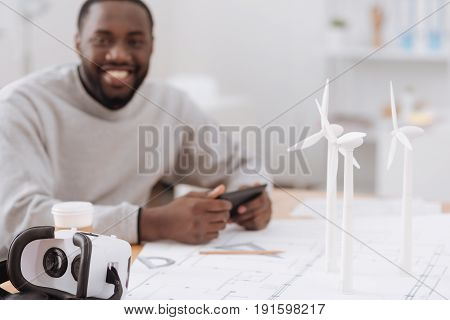Virtual reality glasses. Selective focus of 3d glasses lying on the table with a delighted happy handsome man sitting at the table in the background