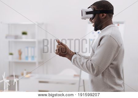 Technological progress. Nice pleasant good looking man wearing virtual reality glasses and using a tablet while experiencing modern technology