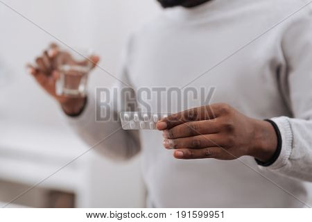 Blister pack of painkillers. Selective focus of a blister pack being in hands of a nice pleasant adult man while taking them