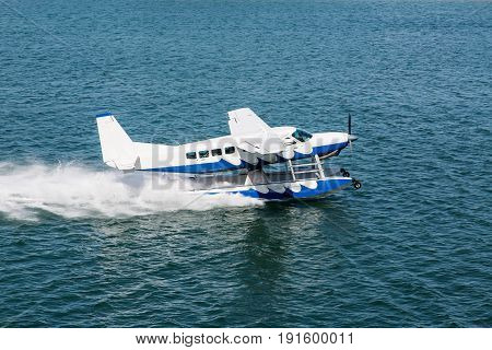 Blue and White Seaplane Taking Off in Aqua Water