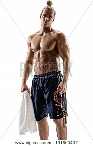 Attractive muscular male with towel and skipping rope on white background. Strength and motivation