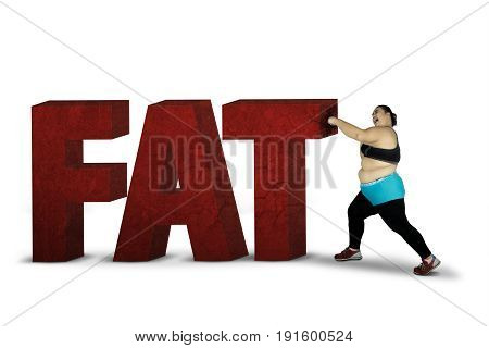 Obese woman crushing word of fat while wearing sportswear isolated on white background