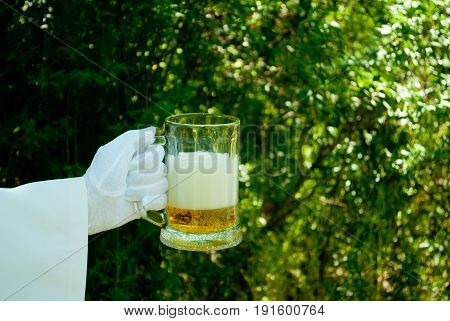 The waiter's hand in a white glove and with a white napkin holds a beer-filled glass beer filled with beer and foam on a blurred background of the nature of trees and bushes