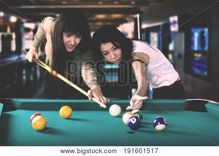 Two pretty multiracial women playing billiards together while aiming on the billiards ball Shot at the bar