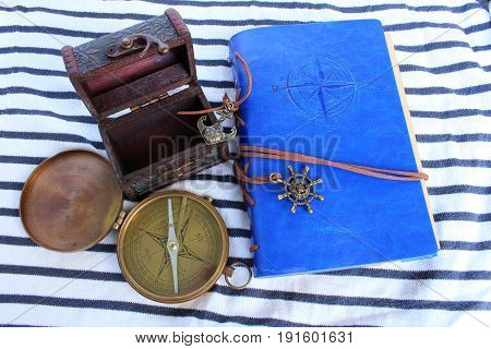 A logbook with a compass and a pirate chest on a seabed