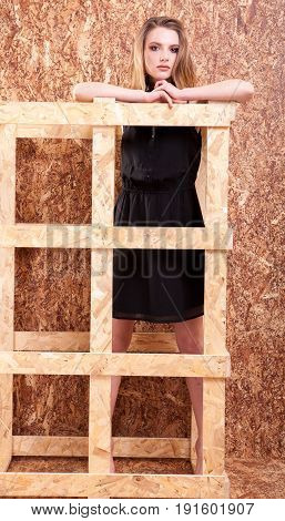 Gorgeous woman fashion style posing on wooden wall in studio photo. Style and vogue