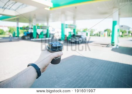 car trip, man with coffee cup going to his car on gas station
