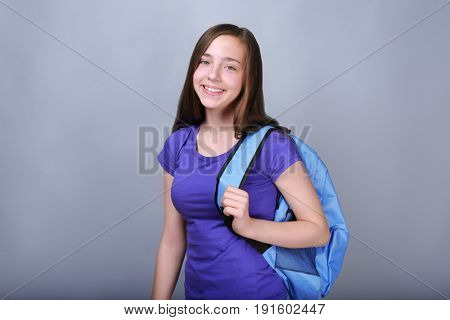 Cute pretty girl with schoolbag on color background