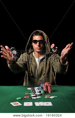 Young man playing poker tossing chips against a black background