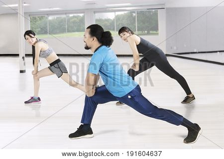 Multi ethnic of young friends doing stretching exercise together in the fitness center