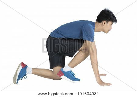 Young man is ready to run while wearing sportswear isolated on white background