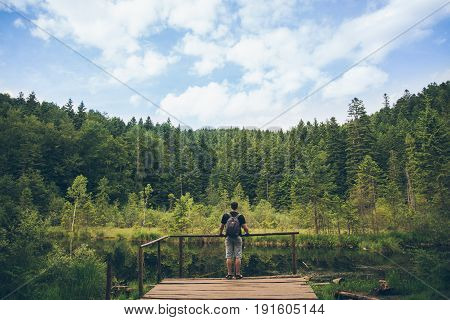 man looks at lake in Carpathian mountains in sunny day