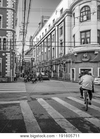 Shanghai, China - Nov 4, 2016: Along Sichuan Road Middle. Cyclists and pedestrians. Street photography in monochrome.